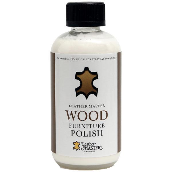 Genomskinlig flaska med svart kork innehållande vitt möbelpolering för trä